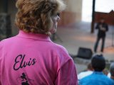 An Elvis festival worker hawks programs on the opening night of the Lake George Elvis Festival.